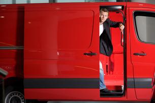 Young man looking through van door, portraitの写真素材 [FYI03655233]