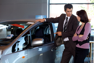 Car salesman explaining car features to customerの写真素材 [FYI03655244]