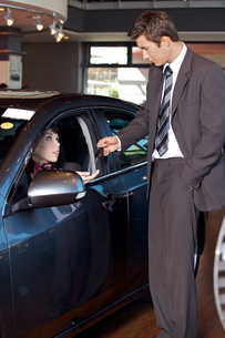Car salesman giving the car keys to a young womanの写真素材 [FYI03655249]