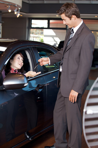 Car salesman giving the car keys to a young womanの写真素材 [FYI03655250]