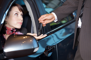 Young woman receiving the car keys from car salesmanの写真素材 [FYI03655251]