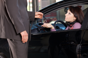 Car salesman giving the car keys to a young womanの写真素材 [FYI03655252]