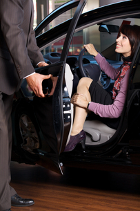 Car salesman giving the car keys to a young womanの写真素材 [FYI03655253]