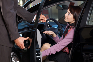 Car salesman giving the car keys to a young womanの写真素材 [FYI03655254]