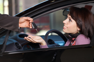 Young woman receiving the car keys from car salesmanの写真素材 [FYI03655255]