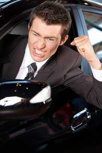 Angry young man clenching his fist, sitting in new carの写真素材 [FYI03655261]