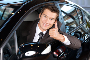 Portrait of man sitting in new car showing thumbs upの写真素材 [FYI03655266]