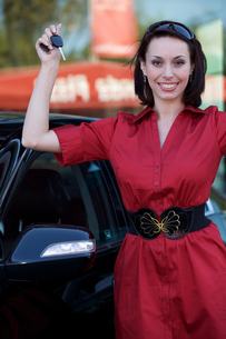Portrait of smiling young woman holding car keyの写真素材 [FYI03655271]