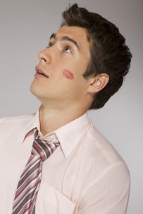 Young caucasian businessman with lipstick kiss mark on his cheekの写真素材 [FYI03655295]