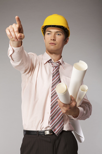 Young caucasian engineer with plans pointing finger awayの写真素材 [FYI03655301]
