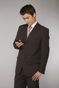 Young caucasian businessman playing with phoneの写真素材 [FYI03655337]