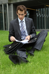 young caucasian businessman sitting on grass with documentsの写真素材 [FYI03655351]