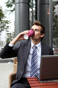 young caucasian businessman using his laptop in cafe - drinkingの写真素材 [FYI03655357]