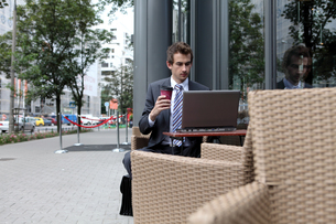 young caucasian businessman using his laptop in cafe - drinkingの写真素材 [FYI03655363]