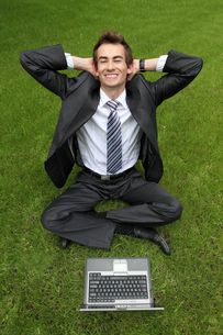young caucasian businessman relaxing on grass with his laptopの写真素材 [FYI03655400]