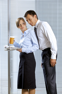 Smiling businessman with woman holding glass of coffee and newspaper in officeの写真素材 [FYI03655429]