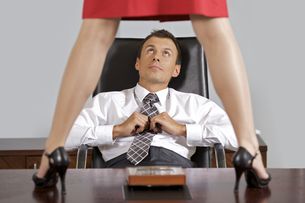 Businesswoman standing on table in front of businessman at officeの写真素材 [FYI03655464]