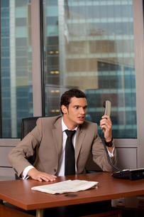 Angry business man holding telephone receiverの写真素材 [FYI03655486]