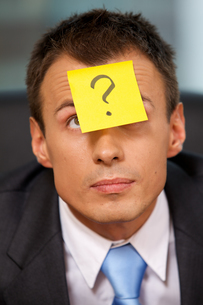Businessman in office with question mark written on adhesive notの写真素材 [FYI03655517]