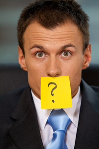 Portrait of businessman in office with question mark written onの写真素材 [FYI03655518]