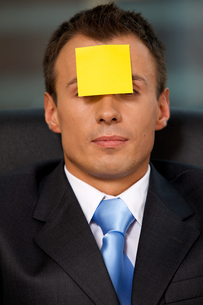 Businessman in office with blank adhesive note stuck to foreheadの写真素材 [FYI03655519]