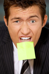 Portrait of businessman in office with blank adhesive note stuckの写真素材 [FYI03655521]