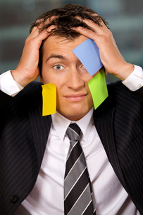 Portrait of businessman in office with blank adhesive notes stuck to his faceの写真素材 [FYI03655522]