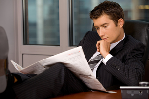 Businessman reading newspaper in office with hand on chinの写真素材 [FYI03655523]
