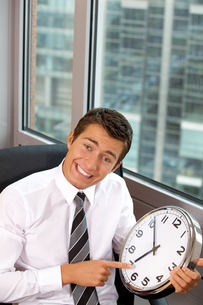 Portrait of smiling businessman pointing at a clockの写真素材 [FYI03655538]