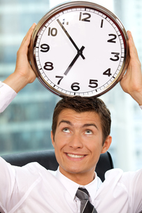 Businessman holding clock to his headの写真素材 [FYI03655540]
