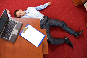 Businessman lying in the officeの写真素材 [FYI03655560]