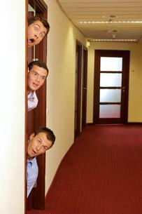 Businessmen peeking out of doorの写真素材 [FYI03655561]