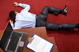 Businessman lying in the officeの写真素材 [FYI03655562]
