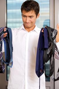 Businessman choosing tie at officeの写真素材 [FYI03655571]