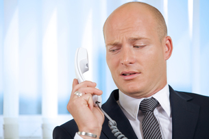 Businessman holding telephone receiver at officeの写真素材 [FYI03655585]