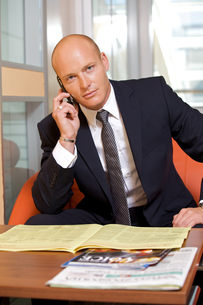 Businessman conversing on mobile phone, portraitの写真素材 [FYI03655607]