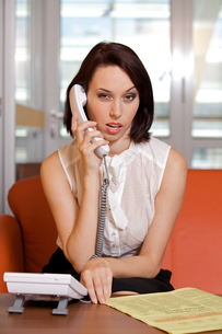 Businesswoman conversing on landline phone, portraitの写真素材 [FYI03655618]
