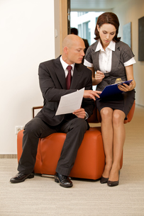 Young confident boss and his secretary looking on documentsの写真素材 [FYI03655695]