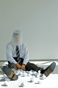 young caucasian businessman with trash bin on his headの写真素材 [FYI03655753]