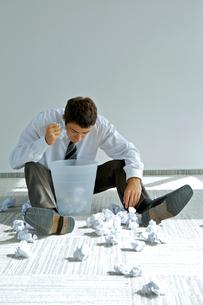 young caucasian businessman seeking document in trash binの写真素材 [FYI03655755]