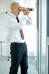 caucasian businessman spying using telescope thru office windowの写真素材 [FYI03655758]