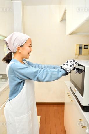 キッチンで料理をする女の子の写真素材 [FYI03655775]