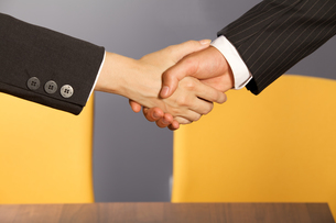 Close-up of businessman and woman shaking hands in officeの写真素材 [FYI03655790]