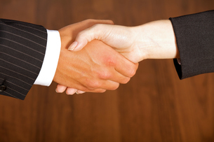 Close-up of businessman and woman shaking hands in officeの写真素材 [FYI03655791]