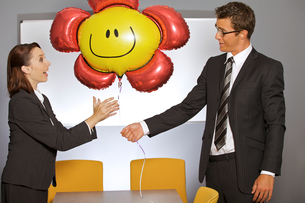 Businessman giving balloon to businesswoman in officeの写真素材 [FYI03655796]