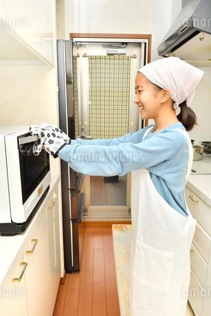 キッチンで料理をする女の子の写真素材 [FYI03655805]