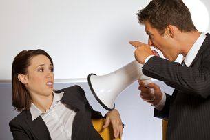 Businessman shouting at businesswoman through megaphone and gesturing gun signの写真素材 [FYI03655807]