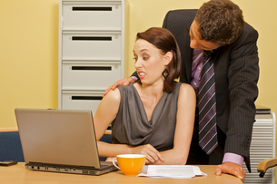 Businessman flirting with businesswoman in officeの写真素材 [FYI03655830]