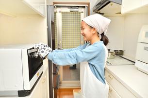キッチンで料理をする女の子の写真素材 [FYI03655835]
