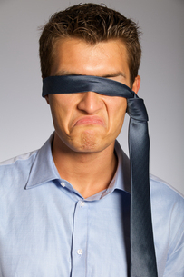 Blindfolded businessman making faceの写真素材 [FYI03655847]